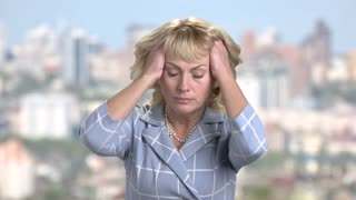 Stressed woman pulling out her hair. Frustrated mature blonde on blurred background. Stress and frustration concept.