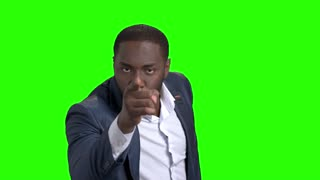 Strict businessman is arguing on green screen. Arrogant dark-skinned man in business suit arguing and pointing with finger on chroma key background.