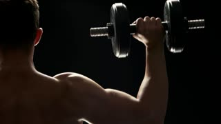 Strong man doing exercises with heavy dumbbells. Close up young sportsman lifting weight on black background, back view.