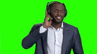 Stylish businessman listening to music in headphones. Portrait of cheerful afro american entrepreneur singing and dancing on Alpha Channel background.