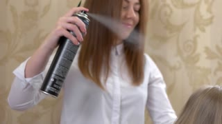 Stylist using hair spray, slow-mo. Girl holding hairspray bottle.