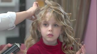 Stylist working with child, hairspray. Cute little girl, hair salon.