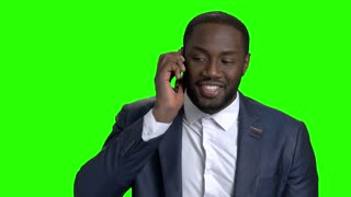Successful businessman talking on mobile phone. Handsome afro american entrepreneur talking on phone on Alpha Channel background.