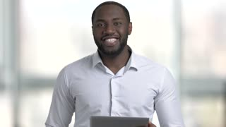 Successful confident african american talking, Black skin man in white dress shirt speaking and explaining holding tablet.