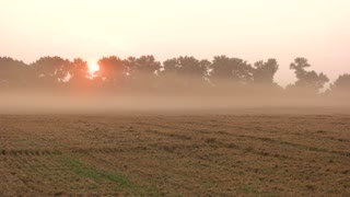 Sunset fast motion. Evening fog above a field. Dust over The ground.