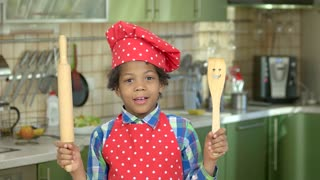 Surprised boy in chef uniform. Kid holding kitchen utensils. Cooking secrets and tips.