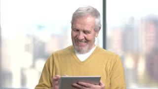 Surprised elderly man using pc tablet. Excited senior man with digital tablet on blurred background.