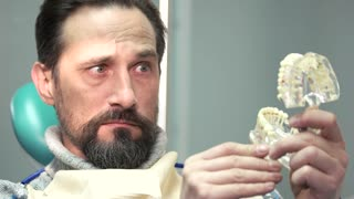 Surprised man holding jaw model. Amazed mature male at dentist. Dental implants at affordable price.