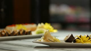 Sushi on long white plate. Yellow flower and sushi rolls. Style and taste. Work of professional chef.