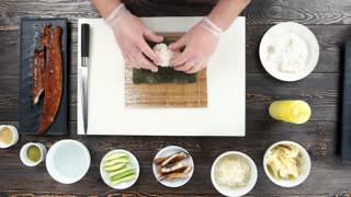 Sushi preparation, rice and nori. Hands making food top view.