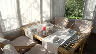 Table with plates and glasses. Summer behind the window. Cheap family restaurant.