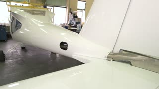 Tail of airplane in workshop. Small white plane.