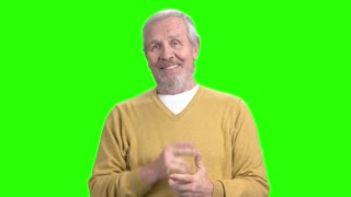 Talking mature man on green screen. Elderly man in casual wear talking to camera on chroma key background.