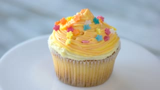 Tasty dessert on white plate. Cupcake with cream cheese and colorful decoration. Yummy pastry at cafe.