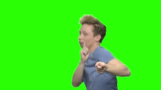 Teenage boy dancing with point fingers. Green hromakey background for keying.