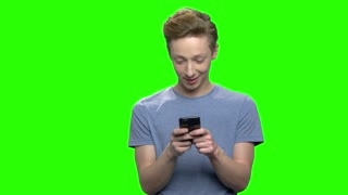 Teenage boy playing video games on smartphone. Green screen hromakey background for keying.