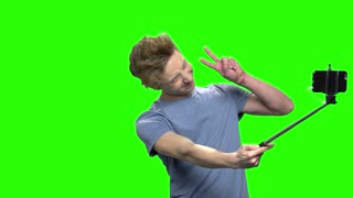 Teenage boy taking selfie picture with mobile phone. Posing for photo. Green screen hromakey background for keying.