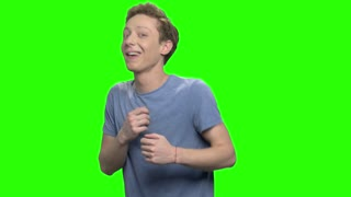 Teenager boy dancing and enjoying music. Green screen hromakey background for keying.