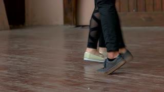 Teenagers legs dancing, close up. Young couple. Wooden rustic floor.