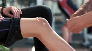 Therapist applying ointment cream on female knee. Fitness trainer massaging injured leg to woman. Sport accident concept.
