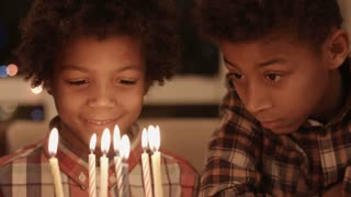Thoughtful boys near birthday cake. Afro kid's small birthday party. Find peace inside yourself. Becoming adult little-by-little.