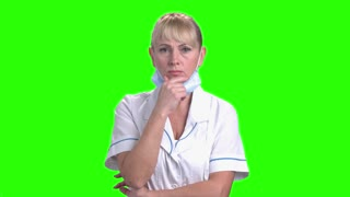 Thoughtful female doctor on green screen. Confident female medical doctor holding chin on hand and thinking on chroma key background.