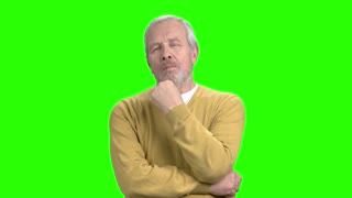 Thoughtful mature man on green screen. Thinking older man, chroma key background.