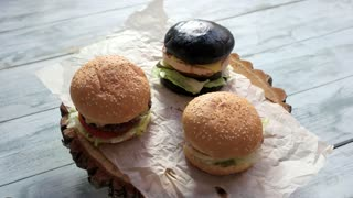 Three burgers on wooden background. Hamburgers with sesame buns. Tasty food at lowest price.