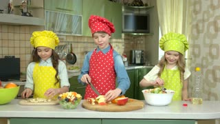 Three children cooking. Girl adding oil to salad.