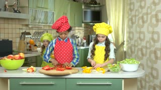 Three children in the kitchen. Kids cutting paprika. How to cook healthy food.