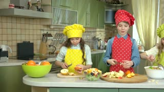 Three kids cooking. Children cutting fruits for salad.