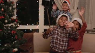 Three kids take Christmas selfie. Three boys taking Christmas selfie. Just smile and wave boys. Remember this day.