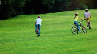 Three young friends cycling in park. Young bikers riding bicycles on green grass. Summer sport and rest.
