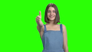 Thumb up and ok gesture. Portrait of teen girl shows signs. Green screen hromakey background for keying.