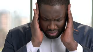 Tired african office worker suffering from headache. Stressed black man in suit feeling headache and massaging head to relax and reduce pain indoor, close up.