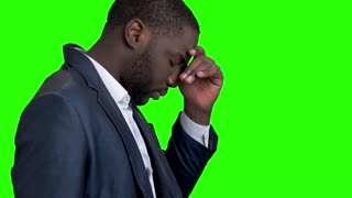 Tired afro american businessman on green screen. Exhausted dark-skinned entrepreneur on Alpha Channel background. Young man having headache.
