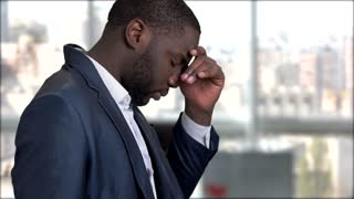 Tired dark-skinned businessman having migraine. Stressed exhausted african-american entrepreneur suffers from headache on blurred background.