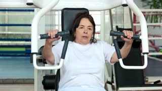 Tired elderly woman at gym. Senior woman wiping with towel after hard sport training on gym equipment. Sport and age.