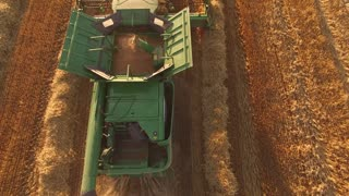Top view of moving combine. Agricultural machine gathers grain. Field of rye. Build business on selling crops.