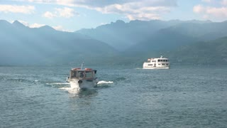Tourist boats on lake Maggiore. Mountains, water and sky.