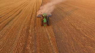 Tractor plowing field, aerial view. Agriculture and technology.