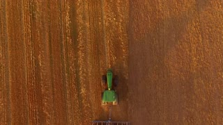Tractor plowing field, top view. Green tractor with a plow.