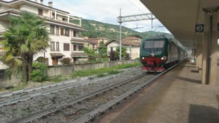 Train near a platform. Railway, town buildings and nature.