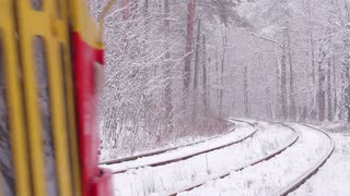 Tram go through the winter wood. The railway in the winter. Snow element.