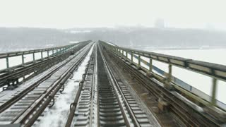 Transportation by rail. Movement of trains on winter bridge. View from the driver's cab.