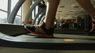 Treadmill in gym. Sportsmen working out in gym. Men running on treadmill.