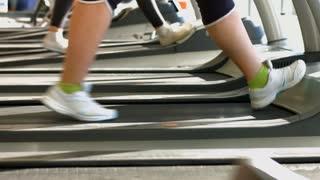 Treadmills in gym hall. Woman's muscular legs on treadmill.