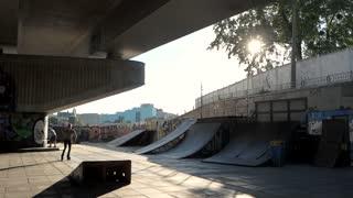 Trick of rollerblader, slow motion. Extreme sportsman on urban background.
