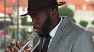 Trumpet player in the street. Trumpeter wearing hat. Music of freedom.