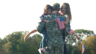 Two adorable little girls with usa backgrounds hug their father. Embracing arrived daddy, meet a hero in the park.